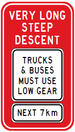 Street sign: Very long steep descent - Trucks and buses must use low gear - Next 7km