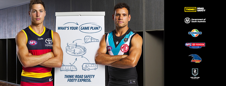"""Two players stand in front of a flipchart with the text """"What's your game plan? Think! Road Safety Footy Express"""". The text is stylised to look like a playbook."""